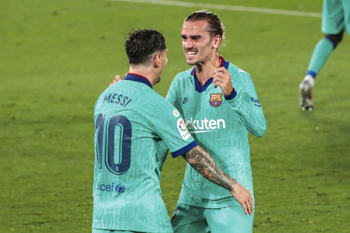 Barcelonas Antoine Griezmann, right, is congratulated by teammate Lionel Messi after scoring his side third goal during the Spanish La Liga soccer match between FC Barcelona and Villareal at La Ceramica stadium in Villareal, Spain, Sunday, July 5, 2020. (AP Photo/Jose Miguel Fernandez)