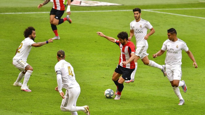 From left to right: Real Madrids Marcelo, Real Madrids Sergio Ramos, Real Madrids Marco Asensio and Real Madrids Casemiro try to stop Athletic Bilbaos Raul Garcia, center, during the Spanish La Liga soccer match between Athletic Club and Real Madrid at the San Manes stadium in Bilbao, Spain, Sunday, July 5, 2020. (AP Photo/Alvaro Barrientos)
