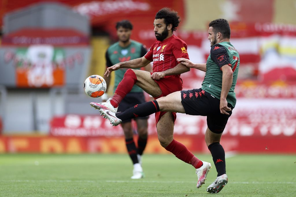 Liverpool's Mohamed Salah vies for the ball with Aston Villa's John McGinn, right, during the English Premier League soccer match between Liverpool and Aston Villa at Anfield Stadium in Liverpool, England, Sunday, July 5, 2020. (Carl Recine/Pool via AP)