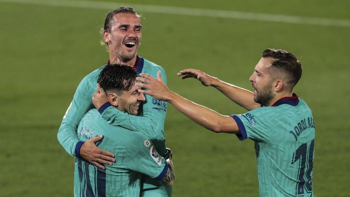 Barcelonas Antoine Griezmann, top, is congratulated by teammate Lionel Messi, left, and Jordi Alba, right, after scoring his side third goal during the Spanish La Liga soccer match between FC Barcelona and Villareal at La Ceramica stadium in Villareal, Spain, Sunday, July 5, 2020. (AP Photo/Jose Miguel Fernandez)