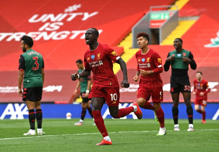 LIVERPOOL, ENGLAND - JULY 05: Sadio Mane of Liverpool celebrates after scoring his teams first goal during the Premier League match between Liverpool FC and Aston Villa at Anfield on July 05, 2020 in Liverpool, England.Football Stadiums around Europe remain empty due to the Coronavirus Pandemic as Government social distancing laws prohibit fans inside venues resulting in games being played behind closed doors. (Photo by Paul Ellis/Pool via Getty Images)