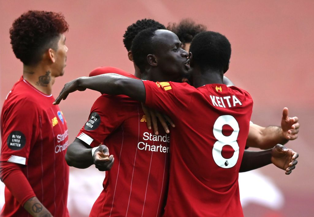 LIVERPOOL, ENGLAND - JULY 05: Sadio Mane of Liverpool celebrates with teammate Naby Keita after scoring his team's first goal during the Premier League match between Liverpool FC and Aston Villa at Anfield on July 05, 2020 in Liverpool, England.Football Stadiums around Europe remain empty due to the Coronavirus Pandemic as Government social distancing laws prohibit fans inside venues resulting in games being played behind closed doors. (Photo by Shaun Botterill/Getty Images)