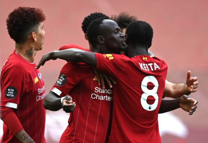 LIVERPOOL, ENGLAND - JULY 05: Sadio Mane of Liverpool celebrates with teammate Naby Keita after scoring his teams first goal during the Premier League match between Liverpool FC and Aston Villa at Anfield on July 05, 2020 in Liverpool, England.Football Stadiums around Europe remain empty due to the Coronavirus Pandemic as Government social distancing laws prohibit fans inside venues resulting in games being played behind closed doors. (Photo by Shaun Botterill/Getty Images)