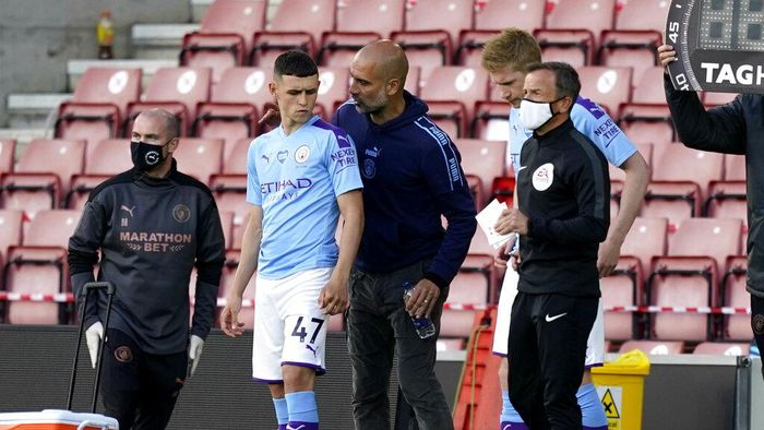 Manchester Citys head coach Pep Guardiola talks with substitute player Phil Foden during the English Premier League soccer match between Southampton and Manchester City at St. Marys Stadium in Southampton, England, Sunday, July 5, 2020. (AP Photo/Will Oliver,Pool)