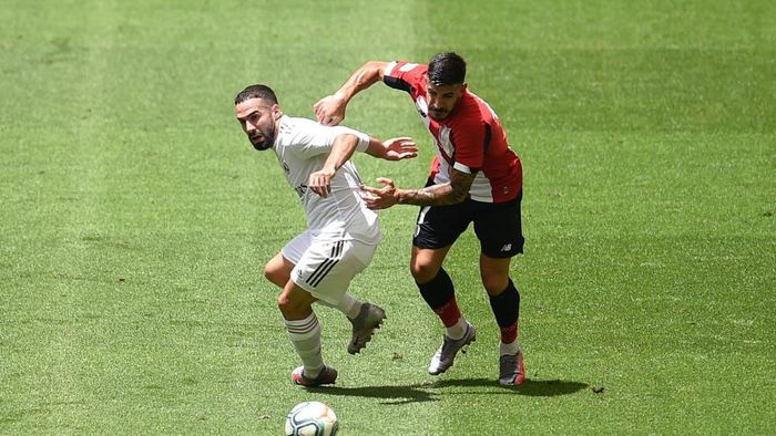 BILBAO, SPAIN - JULY 05: Dani Carvajal of Real Madrid is challenged by Yuri Berchiche of Athletic Club during the La Liga match between Athletic Club and Real Madrid CF at San Mames Stadium on July 05, 2020 in Bilbao, Spain. Football Stadiums around Europe remain empty due to the Coronavirus Pandemic as Government social distancing laws prohibit fans inside venues resulting in all fixtures being played behind closed doors. (Photo by Juan Manuel Serrano Arce/Getty Images)