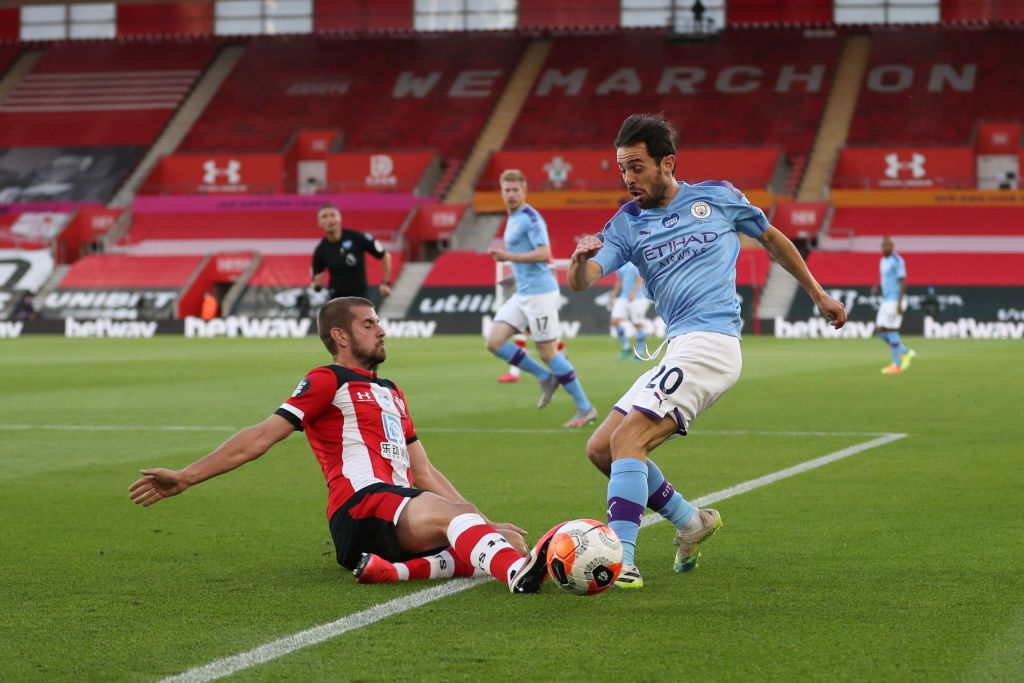 SOUTHAMPTON, ENGLAND - JULY 05: Jack Stephens of Southampton tackles Bernardo Silva of Manchester City during the Premier League match between Southampton FC and Manchester City at St Mary's Stadium on July 05, 2020 in Southampton, England. Football Stadiums around Europe remain empty due to the Coronavirus Pandemic as Government social distancing laws prohibit fans inside venues resulting in games being played behind closed doors. (Photo by Catherine Ivill/Getty Images)