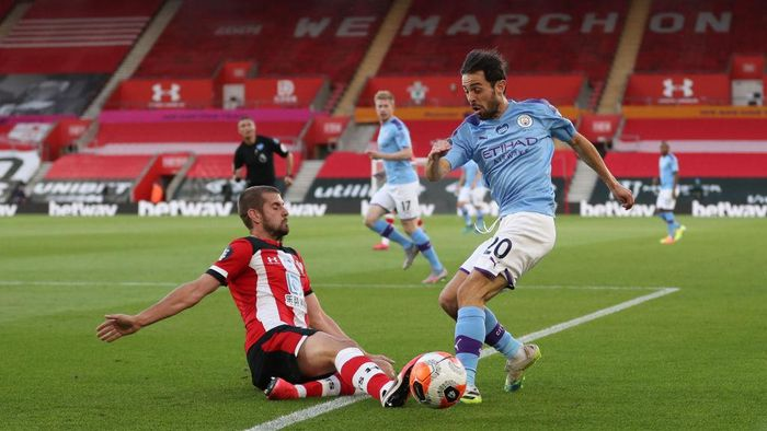 SOUTHAMPTON, ENGLAND - JULY 05: Jack Stephens of Southampton tackles Bernardo Silva of Manchester City during the Premier League match between Southampton FC and Manchester City at St Marys Stadium on July 05, 2020 in Southampton, England. Football Stadiums around Europe remain empty due to the Coronavirus Pandemic as Government social distancing laws prohibit fans inside venues resulting in games being played behind closed doors. (Photo by Catherine Ivill/Getty Images)