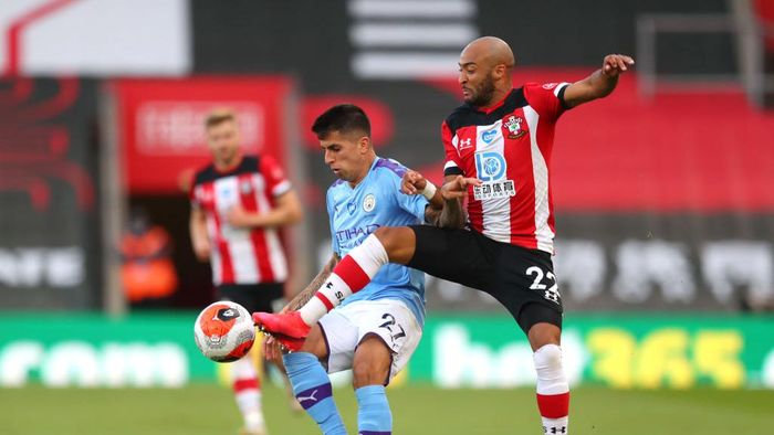 SOUTHAMPTON, ENGLAND - JULY 05: Joao Cancelo of Manchester City is challenged by Nathan Redmond of Southampton during the Premier League match between Southampton FC and Manchester City at St Marys Stadium on July 05, 2020 in Southampton, England. Football Stadiums around Europe remain empty due to the Coronavirus Pandemic as Government social distancing laws prohibit fans inside venues resulting in games being played behind closed doors. (Photo by Catherine Ivill/Getty Images)