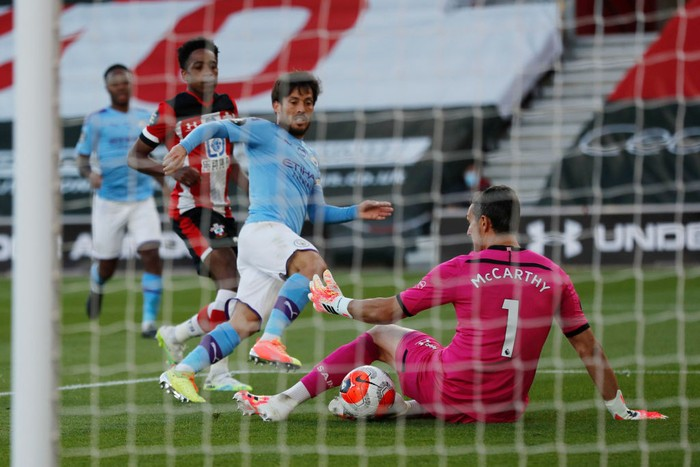 SOUTHAMPTON, ENGLAND - JULY 05: Alex McCarthy of Southampton saves from David Silva of Manchester City during the Premier League match between Southampton FC and Manchester City at St Marys Stadium on July 05, 2020 in Southampton, England. Football Stadiums around Europe remain empty due to the Coronavirus Pandemic as Government social distancing laws prohibit fans inside venues resulting in games being played behind closed doors. (Photo by Frank Augstein/Pool via Getty Images)