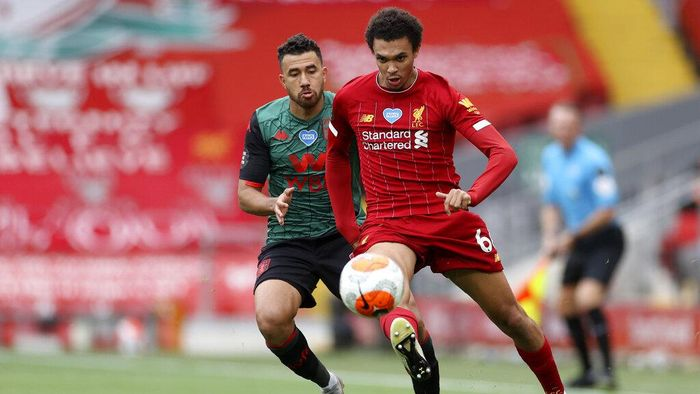 Liverpools Trent Alexander-Arnold controls the ball next to Aston Villas Trezeguet, left, during the English Premier League soccer match between Liverpool and Aston Villa at Anfield Stadium in Liverpool, England, Sunday, July 5, 2020. (Carl Recine/Pool via AP)