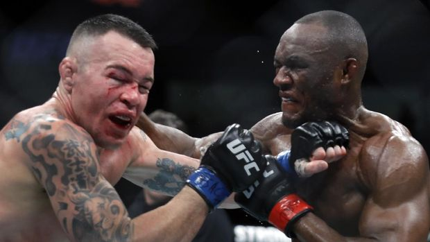 LAS VEGAS, NEVADA - DECEMBER 14: Colby Covington (L) takes a punch from UFC welterweight champion Kamaru Usman in their welterweight title fight during UFC 245 at T-Mobile Arena on December 14, 2019 in Las Vegas, Nevada. Usman retained his title with a fifth-round TKO.   Steve Marcus/Getty Images/AFP
