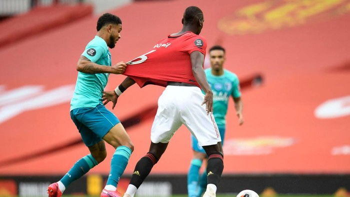 MANCHESTER, ENGLAND - JULY 04: Joshua King of AFC Bournemouth pulls the shirt of Paul Pogba of Manchester United during the Premier League match between Manchester United and AFC Bournemouth  at Old Trafford on July 04, 2020 in Manchester, England. Football Stadiums around Europe remain empty due to the Coronavirus Pandemic as Government social distancing laws prohibit fans inside venues resulting in all fixtures being played behind closed doors. (Photo by Peter Powell/Pool via Getty Images)