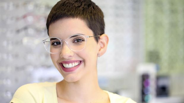 Young woman wearing transparent eyeglasses in an eyewear store. About 25 years old, Caucasian female.