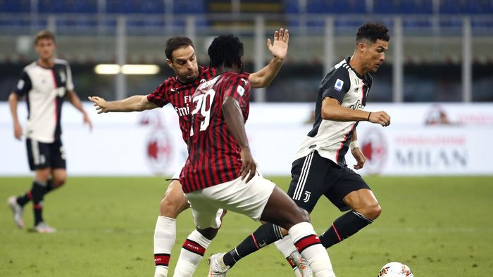 Juventus Cristiano Ronaldo, right, controls the ball by AC Milans Giacomo Bonaventura, left, and Franck Kessie during the Serie A soccer match between AC Milan and Juventus at the San Siro stadium, in Milan, Italy, Tuesday, July 7, 2020. (AP Photo/Antonio Calanni)