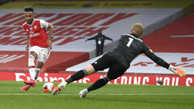 Arsenal's Pierre-Emerick Aubameyang kicks the ball past Leicester's goalkeeper Kasper Schmeichel to score his team's first goal during the English Premier League soccer match between Arsenal and Leicester at Emirates Stadium in London, England, Tuesday, July 7, 2020. (AP Photo/Shaun Botterill,Pool)