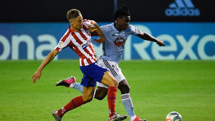 VIGO, SPAIN - JULY 07: Marcos Llorente of Atletico de Madrid competes for the ball with Joseph Aidoo of RC Celta de Vigo during the Liga match between RC Celta de Vigo and Club Atletico de Madrid at Abanca-Balaídos on July 07, 2020 in Vigo, Spain. Football Stadiums around Europe remain empty due to the Coronavirus Pandemic as Government social distancing laws prohibit fans inside venues resulting in all fixtures being played behind closed doors. (Photo by Octavio Passos/Getty Images)