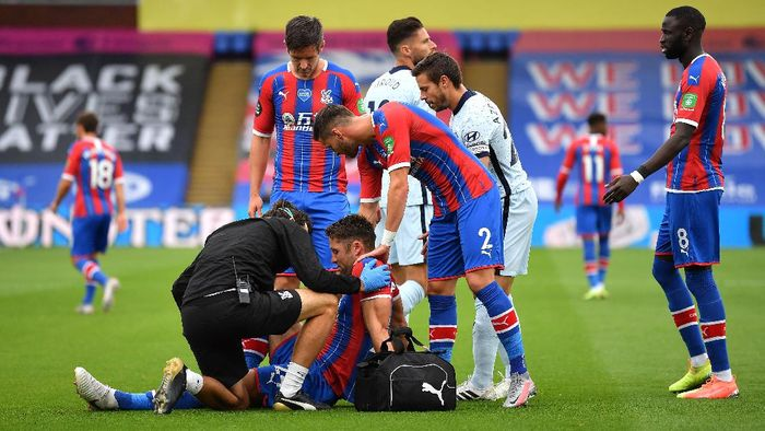 LONDON, ENGLAND - JULY 07: Gary Cahill of Crystal Palace receives medical treatment whilst team mates look on during the Premier League match between Crystal Palace and Chelsea FC at Selhurst Park on July 07, 2020 in London, England. Football Stadiums around Europe remain empty due to the Coronavirus Pandemic as Government social distancing laws prohibit fans inside venues resulting in all fixtures being played behind closed doors. (Photo by Justin Setterfield/Getty Images)