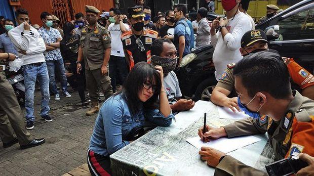 Aparat Satpol PP Jakarta Barat mendata para pengunjung Diskotek Top One yang melanggar aturan PSBB transisi fase 1 di Jakarta, Jumat (3/7/2020). ANTARA/Devi Nindy/aa