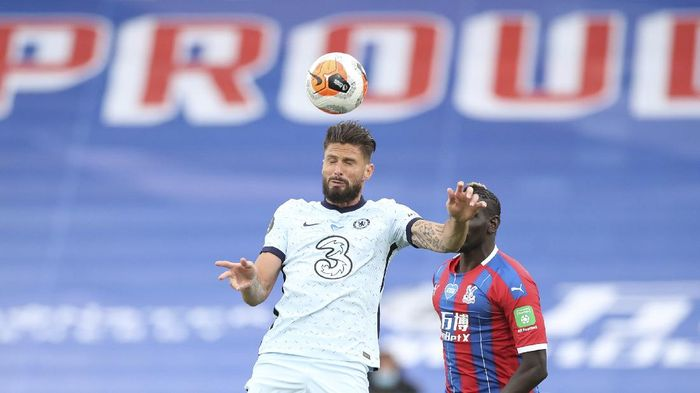 Chelseas Olivier Giroud, left, heads the ball past Crystal Palaces Mamadou Sakho during the English Premier League soccer match between Crystal Palace and Chelsea at Selhurst Park, in London, England, Tuesday, July 7, 2020. (Peter Cziborra/Pool via AP)