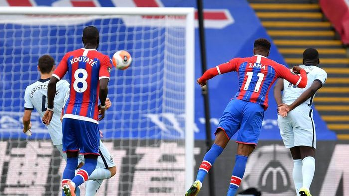 LONDON, ENGLAND - JULY 07: Wilfried Zaha of Crystal Palace scores his teams first goal during the Premier League match between Crystal Palace and Chelsea FC at Selhurst Park on July 07, 2020 in London, England. Football Stadiums around Europe remain empty due to the Coronavirus Pandemic as Government social distancing laws prohibit fans inside venues resulting in all fixtures being played behind closed doors. (Photo by Justin Setterfield/Getty Images)
