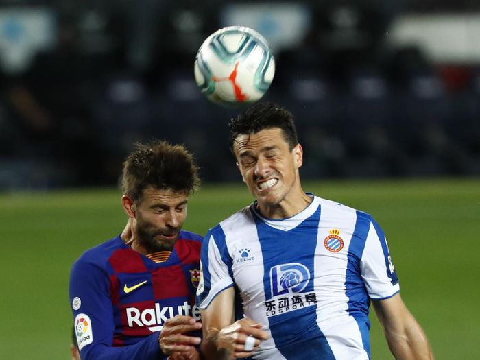 Barcelonas Gerard Pique fights for the ball against Espanyols Bernardo Espinosa during the Spanish La Liga soccer match between FC Barcelona and RCD Espanyol at the Camp Nou stadium in Barcelona, Spain, Wednesday, July 8, 2020. (AP Photo/Joan Monfort)