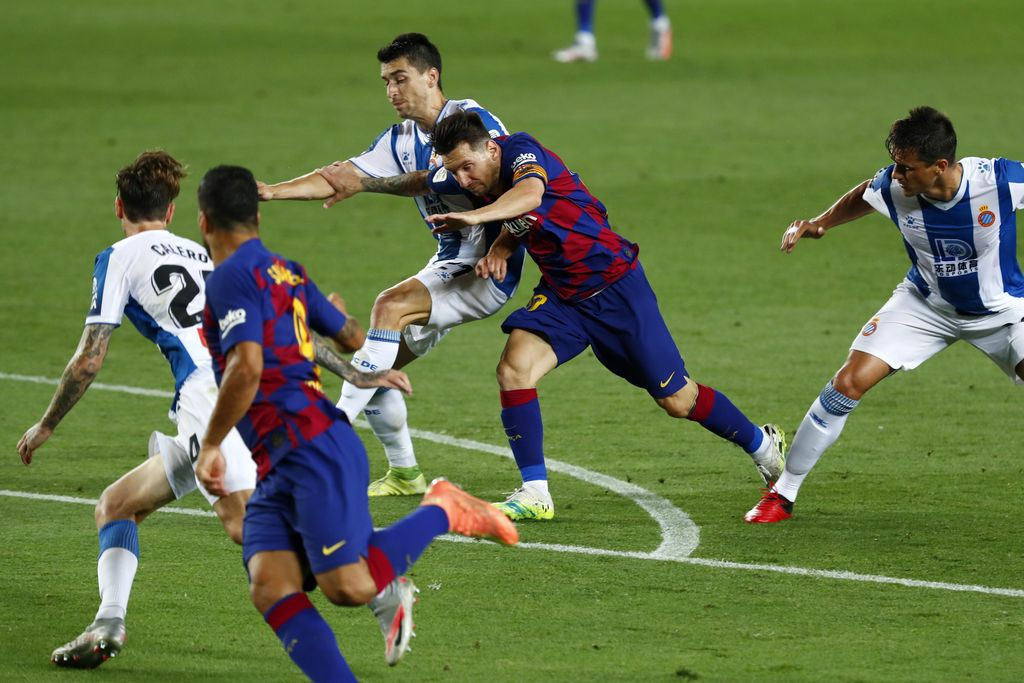 Barcelona's Lionel Messi runs for the ball next to Luis Suarez, against Espanyol's Marc Roca, Fernando Calero and Bernardo Espinosa, left, during the Spanish La Liga soccer match between FC Barcelona and RCD Espanyol at the Camp Nou stadium in Barcelona, Spain, Wednesday, July 8, 2020. (AP Photo/Joan Monfort)
