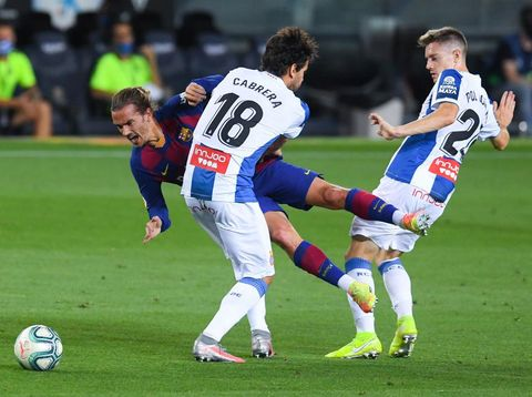 BARCELONA, SPAIN - JULY 08: Antoine Griezmann of FC Barcelona is brought down Leandro Cabrera (L) and Pol Lozano of RCD Espanyol during the Liga match between FC Barcelona and RCD Espanyol at Camp Nou on July 08, 2020 in Barcelona, Spain. Football Stadiums around Europe remain empty due to the Coronavirus Pandemic as Government social distancing laws prohibit fans inside venues resulting in all fixtures being played behind closed doors. (Photo by Alex Caparros/Getty Images)