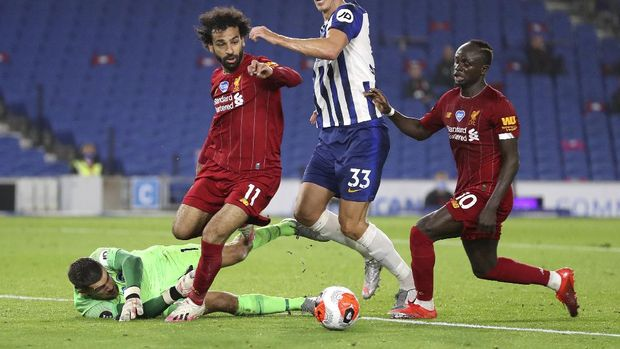 Liverpool's Mohamed Salah and teammate Sadio Mane, right, contest for the ball with Brighton's goalkeeper Mathew Ryan, left, and Dan Burn during the English Premier League soccer match between Brighton and Liverpool at Falmer Stadium in Brighton, England, Wednesday, July 8, 2020. (AP Photo/Catherine Ivill,Pool)
