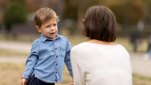 Cute little boy complaining to mother outdoors. Selective focus