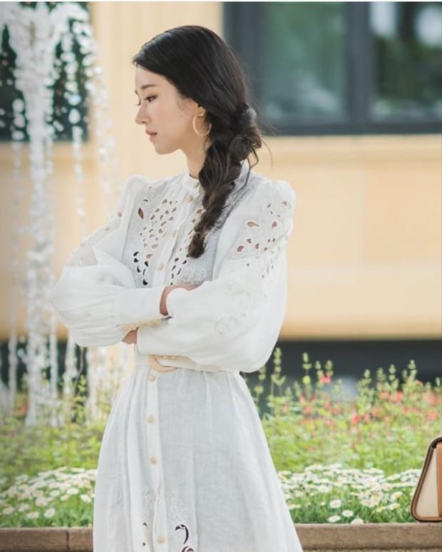 Seo Ye Ji mengenakan long dress putih dengan detail kancing di bagian depan yang mencapai bawah dress.