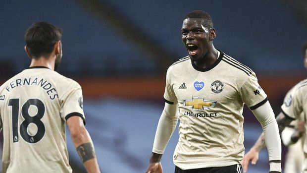 Manchester United's Paul Pogba, right, celebrates after scoring his team's third goal during the English Premier League soccer match between Aston Villa and Manchester United at Villa Park in Birmingham, England, Thursday, July 9, 2020. (AP Photo/Shaun Botterill,Pool)