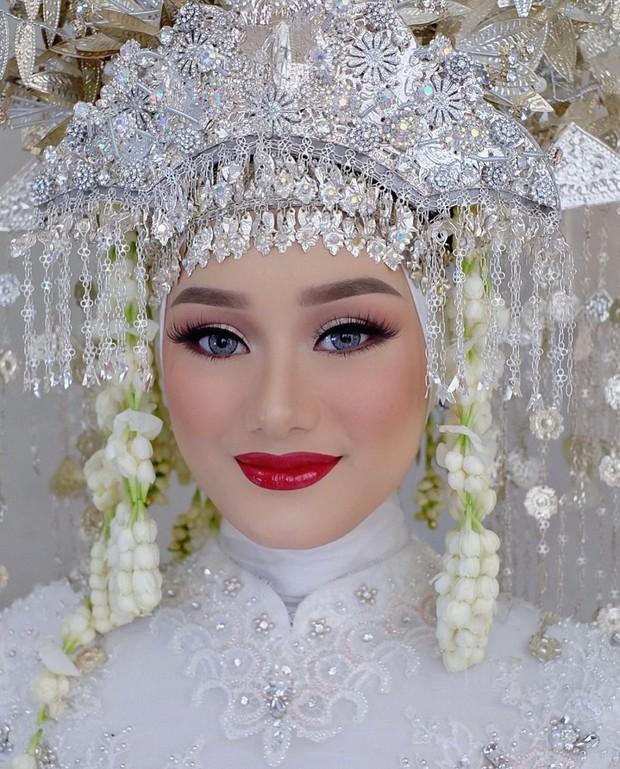Dinda tampil cantik dan anggun dalam balutan kebaya putih bertabur payet serta makeup bold.