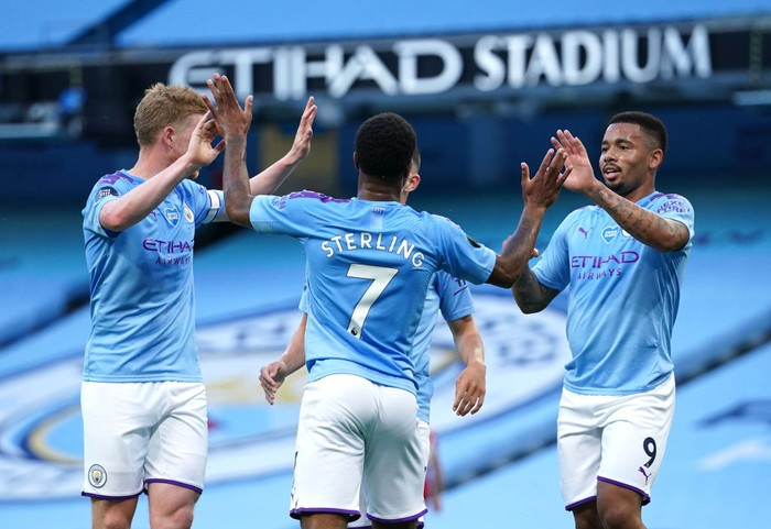MANCHESTER, ENGLAND - JULY 02: Raheem Sterling of Manchester City celebrates with Kevin De Bruyne and Gabriel Jesus after scoring his teams second goal during the Premier League match between Manchester City and Liverpool FC at Etihad Stadium on July 02, 2020 in Manchester, England. Football Stadiums around Europe remain empty due to the Coronavirus Pandemic as Government social distancing laws prohibit fans inside venues resulting in all fixtures being played behind closed doors. (Photo by Dave Thompson/Pool via Getty Images)