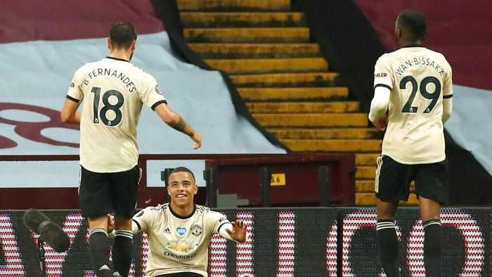 Manchester Uniteds Mason Greenwood celebrates with teammates Bruno Fernandes, left, and Aaron Wan-Bissaka, right, after scoring his teams second goal during the English Premier League soccer match between Aston Villa and Manchester United at Villa Park in Birmingham, England, Thursday, July 9, 2020. (AP PhotoAndrew Boyers,Pool)