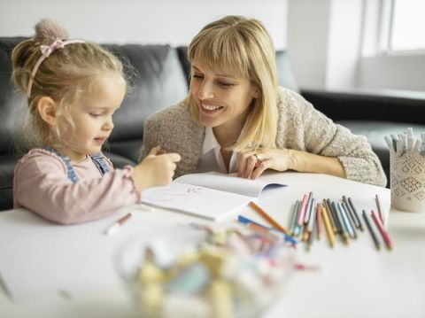 Happy mother and smiling daughter together painting  using marks