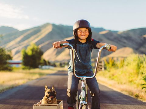 A young boy with vintage clothing and motorcycle helmet rides his stingray bicycle with his pet and best friend French Bulldog riding along in a side car in Utah, USA. Sometimes a road trip journey with your best friend and some fresh air in your face is the best medicine for the soul.