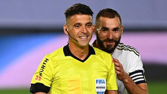 Real Madrids French forward Karim Benzema (R) jokes with Spanish referee Jesus Gil during the Spanish League football match between Real Madrid and Alaves at the Alfredo Di Stefano stadium in Valdebebas near Madrid on July 10, 2020. (Photo by GABRIEL BOUYS / AFP)