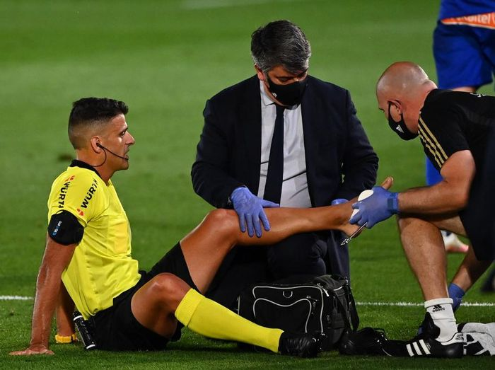 Spanish referee Jesus Gil (L) receives medical attention during the Spanish League football match between Real Madrid and Alaves at the Alfredo Di Stefano stadium in Valdebebas near Madrid on July 10, 2020. (Photo by GABRIEL BOUYS / AFP)