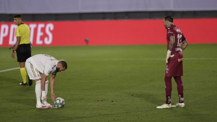 Real Madrids Karim Benzema, left, prepares to shoot a penalty, as Deportivo Alaves goalkeeper Roberto, looks on during the Spanish La Liga soccer match between Real Madrid and Deportivo Alaves at the Alfredo di Stefano stadium in Madrid, Spain, Friday, July 10, 2020. Benzema went on to score the penalty. (AP Photo/Bernat Armangue)