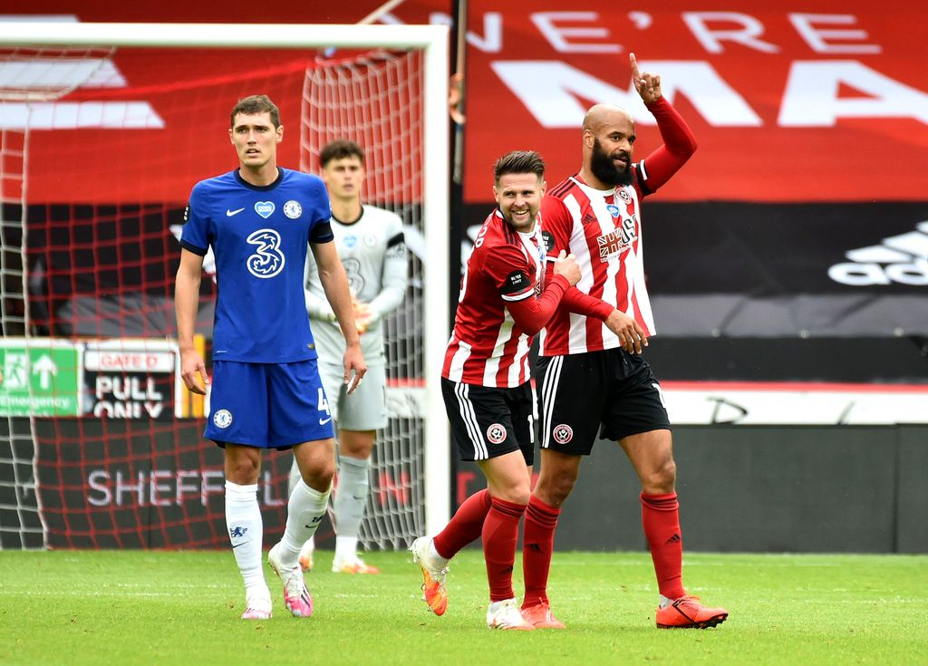 SHEFFIELD, ENGLAND - JULY 11: David McGoldrick of Sheffield United celebrates with teammate Ollie Norwood after scoring his team's first goal during the Premier League match between Sheffield United and Chelsea FC at Bramall Lane on July 11, 2020 in Sheffield, England. Football Stadiums around Europe remain empty due to the Coronavirus Pandemic as Government social distancing laws prohibit fans inside venues resulting in all fixtures being played behind closed doors. (Photo by Rui Vieira/Pool via Getty Images)