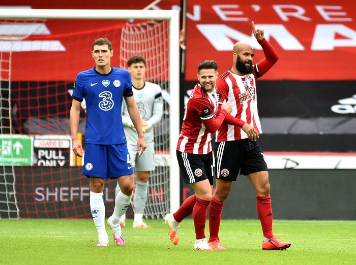 SHEFFIELD, ENGLAND - JULY 11: David McGoldrick of Sheffield United celebrates with teammate Ollie Norwood after scoring his teams first goal during the Premier League match between Sheffield United and Chelsea FC at Bramall Lane on July 11, 2020 in Sheffield, England. Football Stadiums around Europe remain empty due to the Coronavirus Pandemic as Government social distancing laws prohibit fans inside venues resulting in all fixtures being played behind closed doors. (Photo by Rui Vieira/Pool via Getty Images)