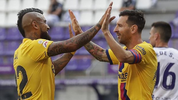 Barcelona's Arturo Vidal, left, celebrates with his teammate Lionel Messi after scoring his side's first goal during the Spanish La Liga soccer match between Valladolid and FC Barcelona at the Jose Zorrilla stadium in Valladolid, Spain, Saturday, July 11, 2020. (AP Photo/Manu Fernandez)