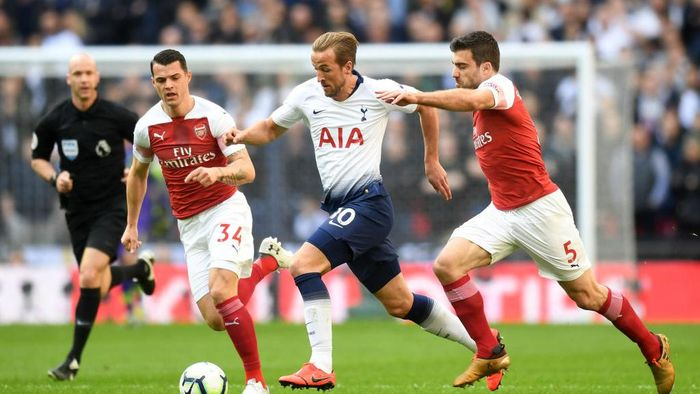 LONDON, ENGLAND - MARCH 02: Harry Kane of Tottenham Hotspur battles for possession with Sokratis Papastathopoulos and Granit Xhaka of Arsenal during the Premier League match between Tottenham Hotspur and Arsenal FC at Wembley Stadium on March 02, 2019 in London, United Kingdom. (Photo by Michael Regan/Getty Images)