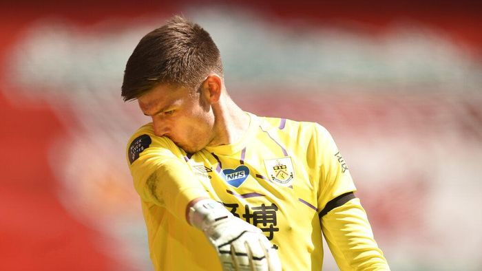 Burnleys goalkeeper Nick Pope wipes his face with his sleeve during the English Premier League soccer match between Liverpool and Burnley at Anfield, Liverpool, England, Saturday, July 11, 2020. (Oli Scarff/ Pool via AP)