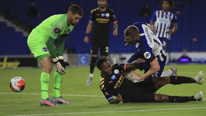 Manchester Citys Raheem Sterling, bottom scores his sides fifth goal during the English Premier League soccer match between Brighton and Manchester City at the Falmer stadium in Brighton, England, Saturday, July 11, 2020. (Adam Davy/Pool via AP)
