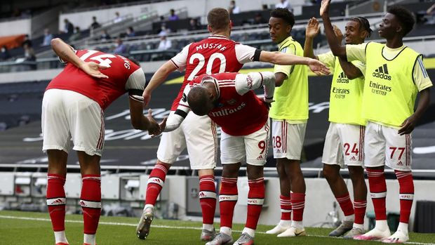 Arsenal's Alexandre Lacazette, center, celebrates with Pierre-Emerick Aubameyang, left, after scoring the opening goal during the English Premier League soccer match between Tottenham Hotspur and Arsenal at the Tottenham Hotspur Stadium in London, England, Sunday, July 12, 2020. (Tim Goode/Pool via AP)