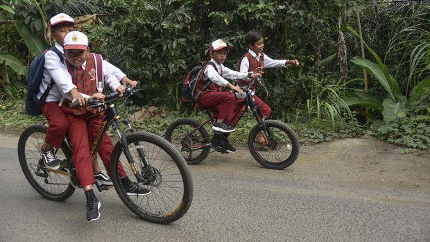 Sejumlah siswa SD mengayuh sepedanya saat pulang dari sekolahnya di Desa Bukit Tinggi, Kecamatan Gunungsari, Lombok Barat, NTB, Senin (13/7/2020). Pada hari pertama masuk sekolah di sebagian besar satuan pendidikan di wilayah NTB belum melaksanakan Kegiatan Belajar Mengajar (KBM) tatap muka dan masih dilakukan dari rumah secara daring atau bentuk lain memanfaatkan segala sumber daya yang dimiliki secara optimal karena kasus COVID-19 di NTB masih tinggi. ANTARA FOTO/Ahmad Subaidi/wsj.