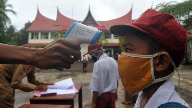 Guru memeriksa suhu tubuh murid saat hari pertana masuk sekolah di SDN 11 Marunggi, Pariaman, Sumatera Barat, Senin (13/7/2020). Kota Pariaman bersama Kabupaten Pesisir Selatan, Kota Sawahlunto dan Kabupaten Pasaman Barat merupakan empat daerah di zona hijau di Sumatera Barat yang sudah memulai aktivitas belajar-mengajar di sekolah dengan pola tatap muka langsung dan menerapkan protokol kesehatan COVID-19. ANTARA FOTO/Iggoy el Fitra/wsj.