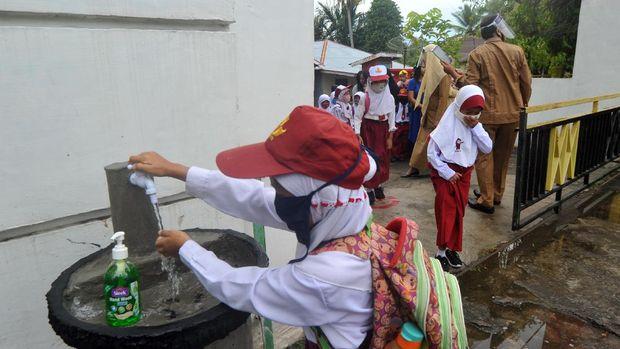Sejumlah murid mencuci tangan sebelum masuk hari pertama sekolah di SDN 11 Marunggi Pariaman, Sumatera Barat, Senin (13/7/2020). Kota Pariaman bersama Kabupaten Pesisir Selatan, Kota Sawahlunto dan Kabupaten Pasaman Barat merupakan empat daerah di zona hijau di Sumatera Barat yang sudah memulai aktivitas belajar-mengajar di sekolah dengan pola tatap muka langsung dan menerapkan protokol kesehatan COVID-19. ANTARA FOTO/Iggoy el Fitra/wsj.