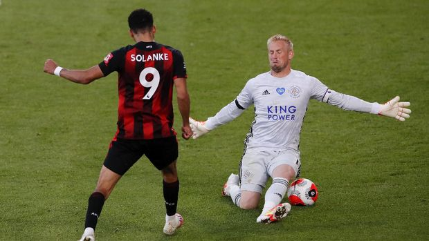 Bournemouth's Dominic Solanke, left, kicks the ball past Leicester's goalkeeper Kasper Schmeichel to score his team's fourth goal during the English Premier League soccer match between Bournemouth and Leicester City at Vitality Stadium in Bournemouth, England, Sunday, July 12, 2020.(AP Photo/Andy Couldridge,Pool)